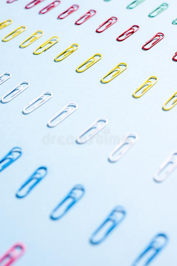 Multi-colored paper clips in row. On blue background royalty free stock photo