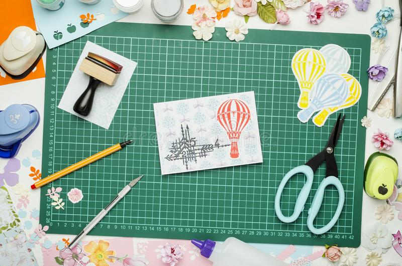 Multi-colored paper, homemade postcard and scrapbooking tools and materials on green mat for cutting. Top view, no hands royalty free stock photography