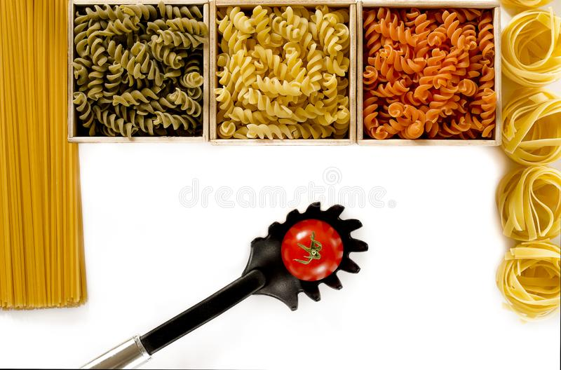 Multi-colored pasta in the form of spirals lie in wooden boxes that stand on a white table royalty free stock photo