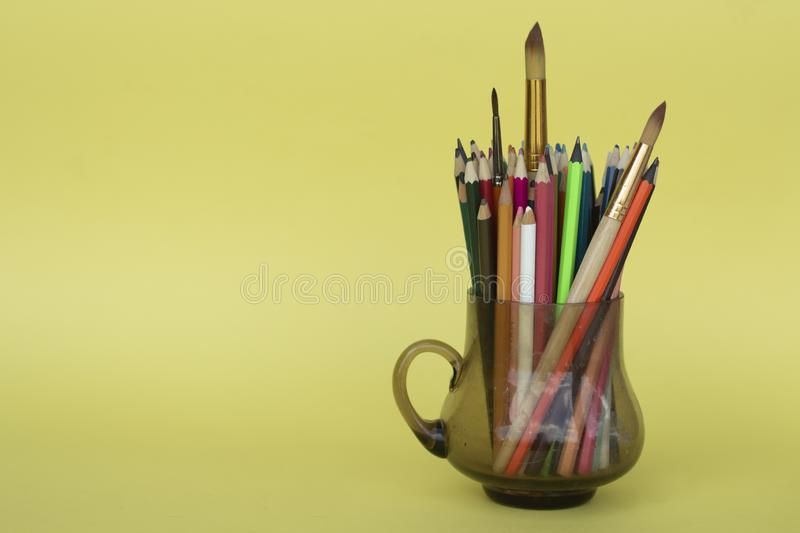 Multi-colored pencils in a transparent glass mug isolated on yellow. Children creativity. stock images