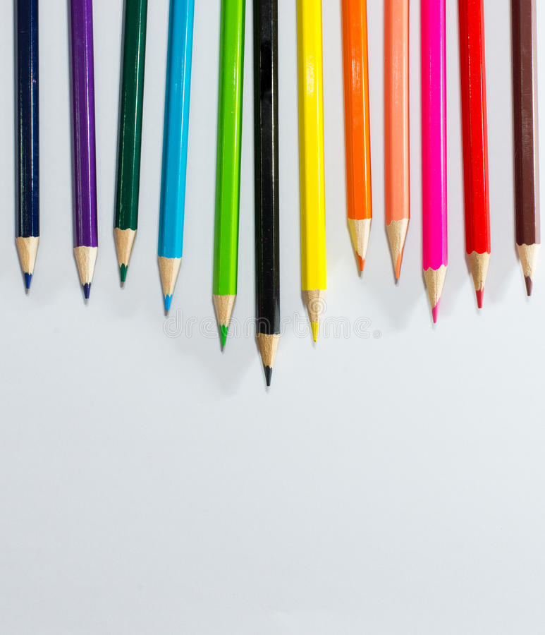 Multi colored pencils on a white background with space for text stock photos