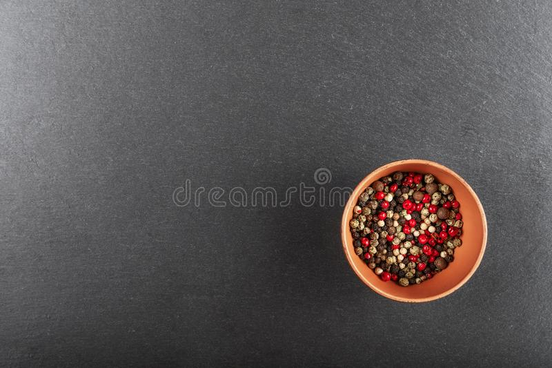 Multi-colored pepper on a black background. Multi colored pepper peas in a clay plate in the center on a black background, top view stock photos