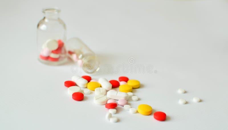 Multi-colored pillen in transparante glasflessen, op een witte achtergrond Het concept geneeskunde, behandeling royalty-vrije stock afbeelding