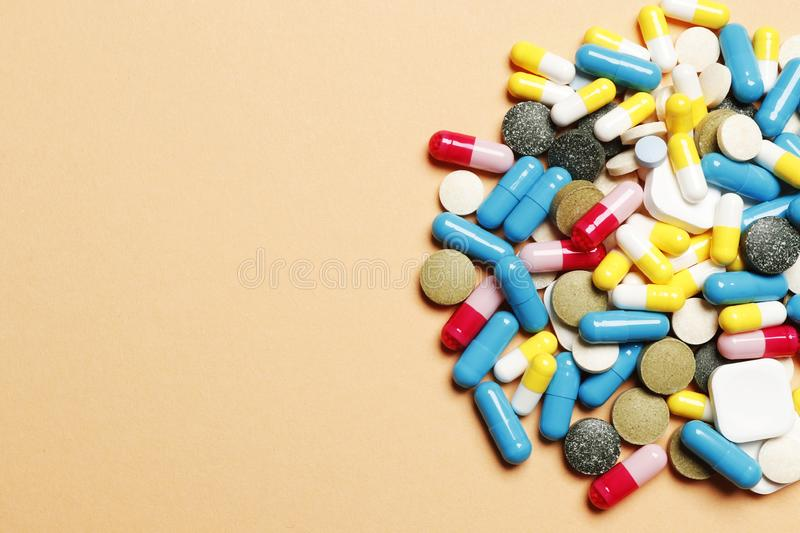 Multi-colored pills on a pink background stock image