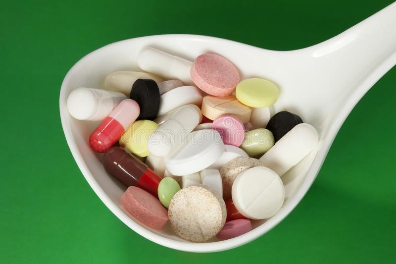 Multi colored pills in white spoon stock image