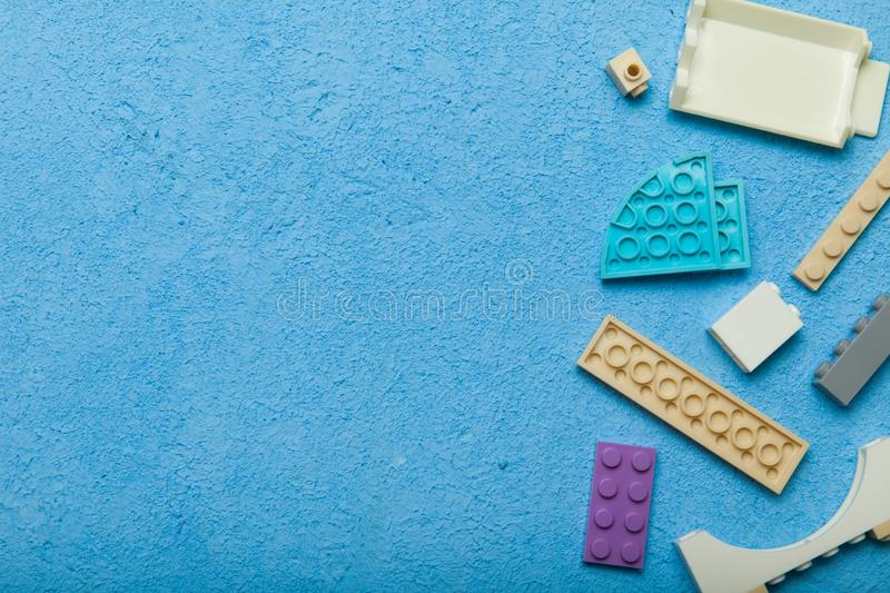 A multi-colored plastic building toy. Children`s constructor on a blue background. Empty space for text.  royalty free stock images