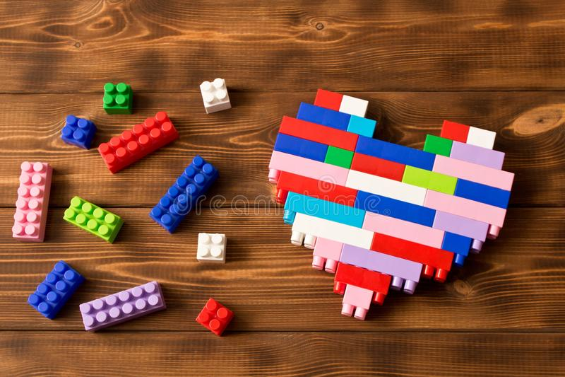 Multi-colored plastic construction set on the wooden table . Children`s educational games. Close up.  stock photo