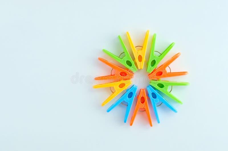 Multi-colored plastic die wasknijpers in de vorm van cirkel worden gevoerd Witte achtergrond stock afbeeldingen
