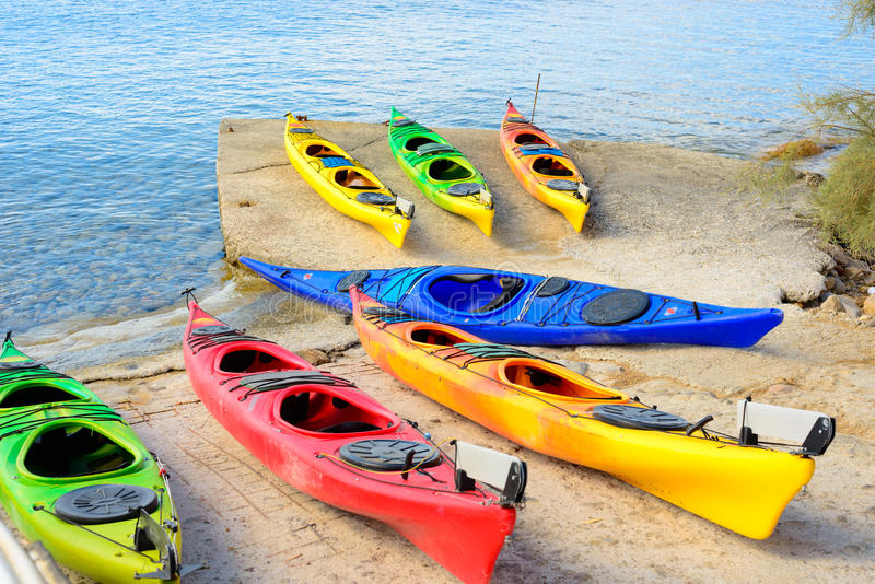 Multi-colored plastic kayaks. Arranged on a cement pier ready to be taken out on the water royalty free stock image