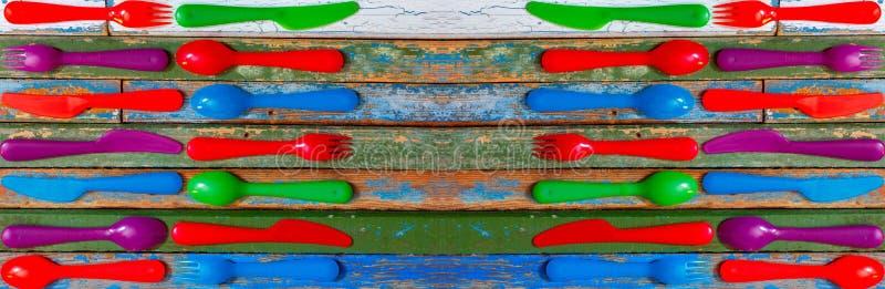 Multi-colored plastic lepels, vorken en messen op een oude houten gekleurde achtergrond stock afbeeldingen