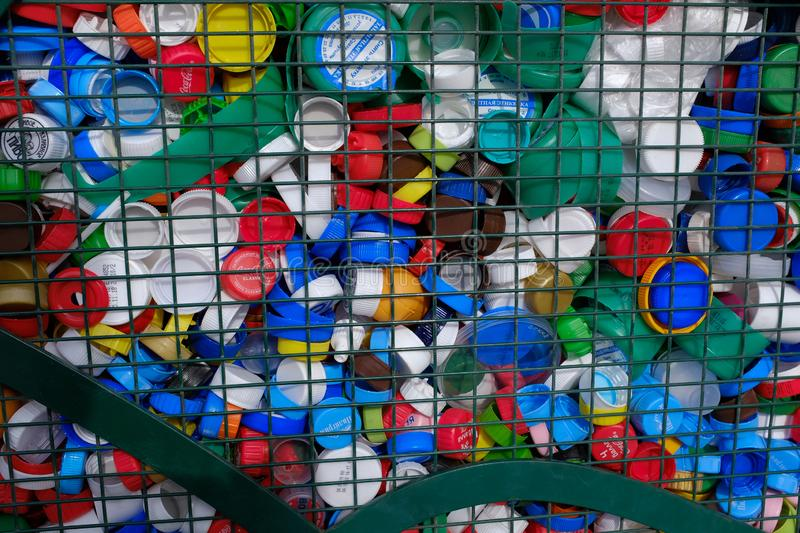 Multi-colored plastic screw caps from bottles behind an iron grid. Concept: waste management, environmental protection, separate stock photography