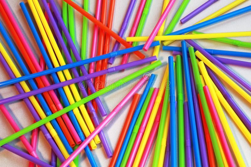 Multi colored plastic straws spread on a table, full frame. High angle view stock image