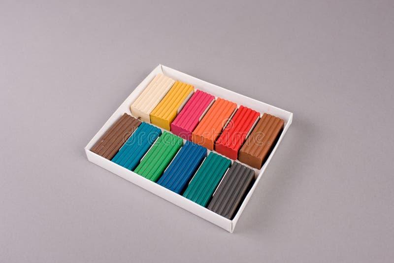 Multi colored plasticine in box on grey. Close up of multi colored plasticine in box on grey stock images