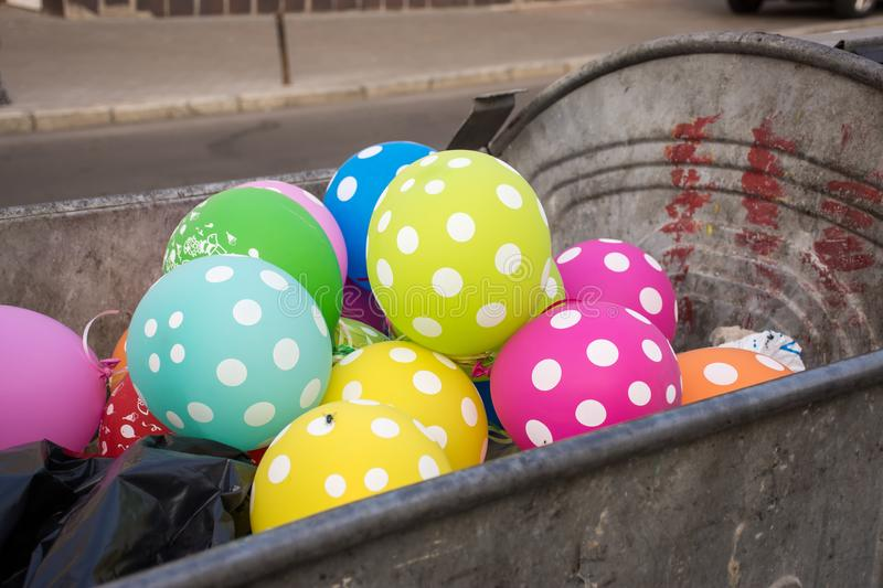 Multi-colored polka dot balloons are in the dumpster or garbage container and on one one sits fly. Party, celebration, fun, holida. Y, birthday for adult or royalty free stock photos