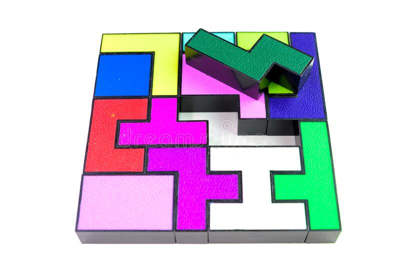 Multi-colored puzzle made of plastic blocks, that`s missing one piece, isolated on white background. Multi-colored puzzle made of plastic blocks, that`s missing stock photo