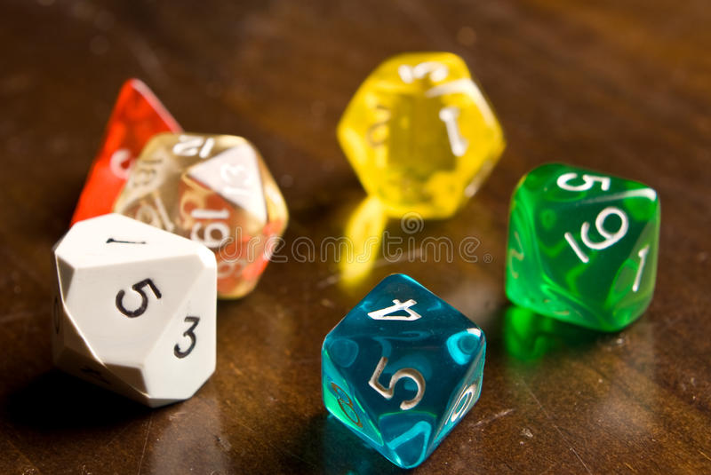 Role Play style dice. Multi-colored role play dice sitting on a wooden table top taken from a low angle. Side lighting and depth of field used to add drama to stock photo
