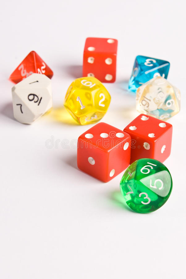 Role Play style dice. Multi-colored role play dice sitting on a wooden table top taken from a low angle. Side lighting and depth of field used to add drama to royalty free stock photo