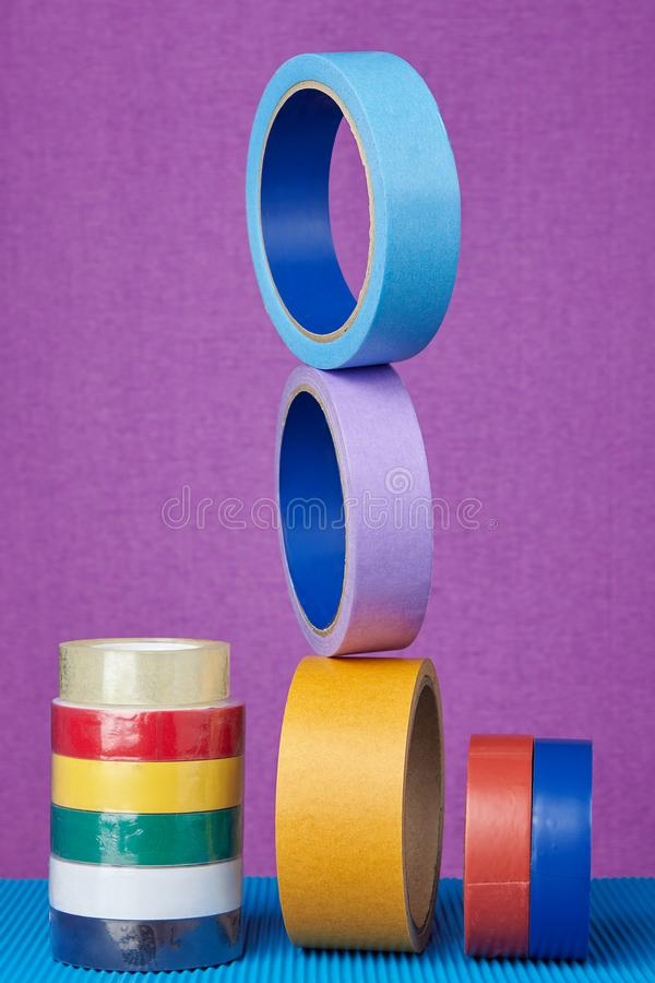 Multi-colored rollers of adhesive tape on purple background. royalty free stock photography