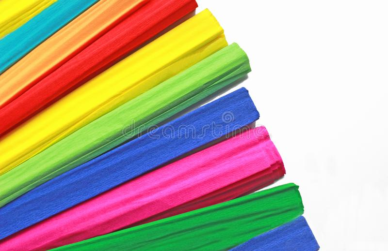 Multi colored rolls of crepe paper fanned out. On white background stock photography