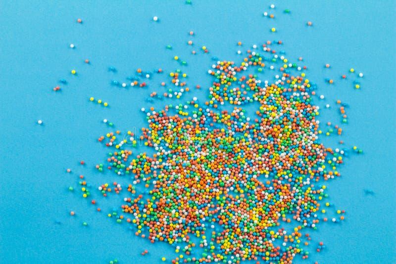 Multi-colored ronde bestrooit opgehoopt die en op blauwe achtergrond verspreidt zich - conceptuele abstracte achtergrond stock fotografie