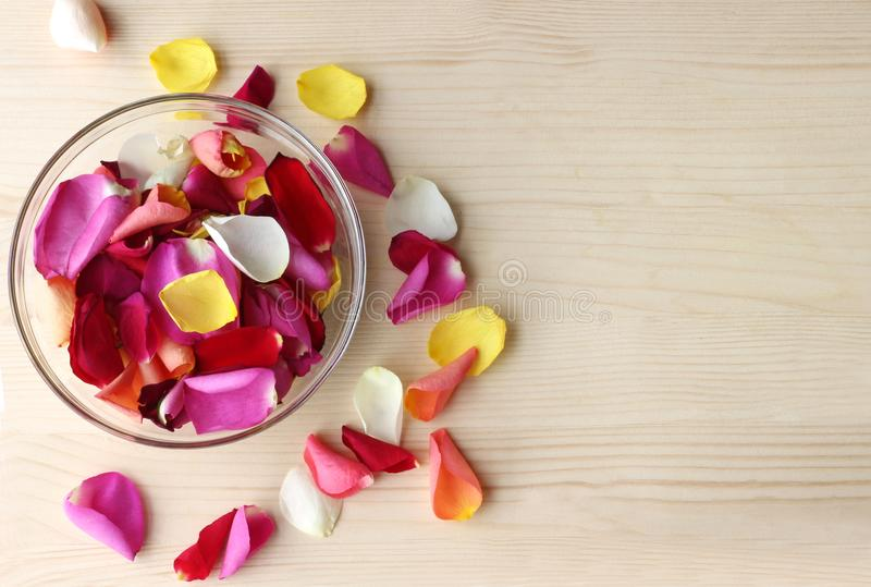 Multi colored rose petals in a glass bowl stock photos