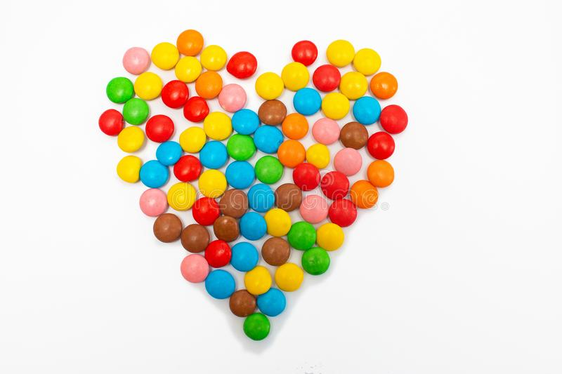 Multi-colored round candy tablets are collected in the form of a heart on a white background for Valentine`s Day stock photography