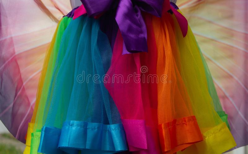 Multi-colored satin skirt. with two color bows. A skirt of red, orange, blue, blue, yellow, green and pink fabric with pink and. Purple bows stock photos