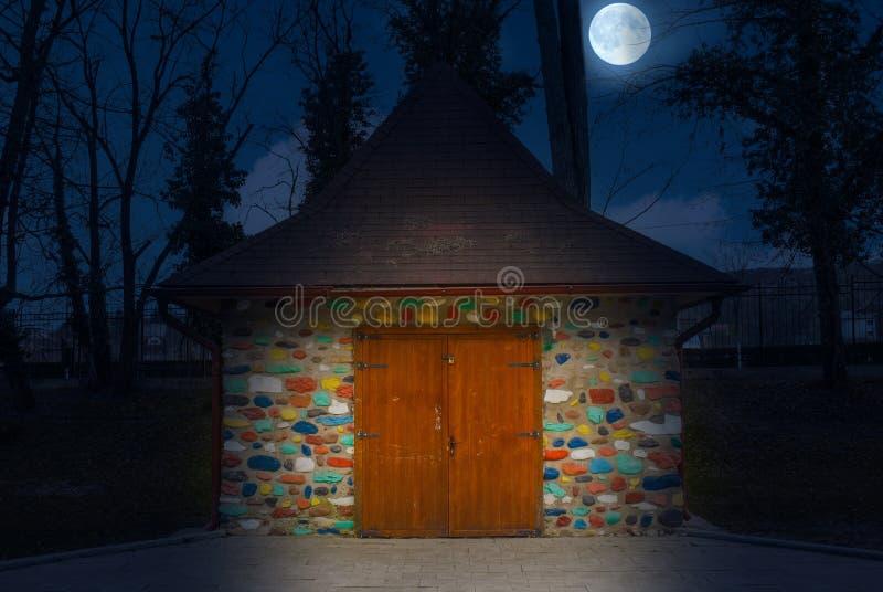 Multi-colored schilderde weinig huis bij nacht met volle maan Kleurrijk steenhuis als in sprookjes stock afbeeldingen
