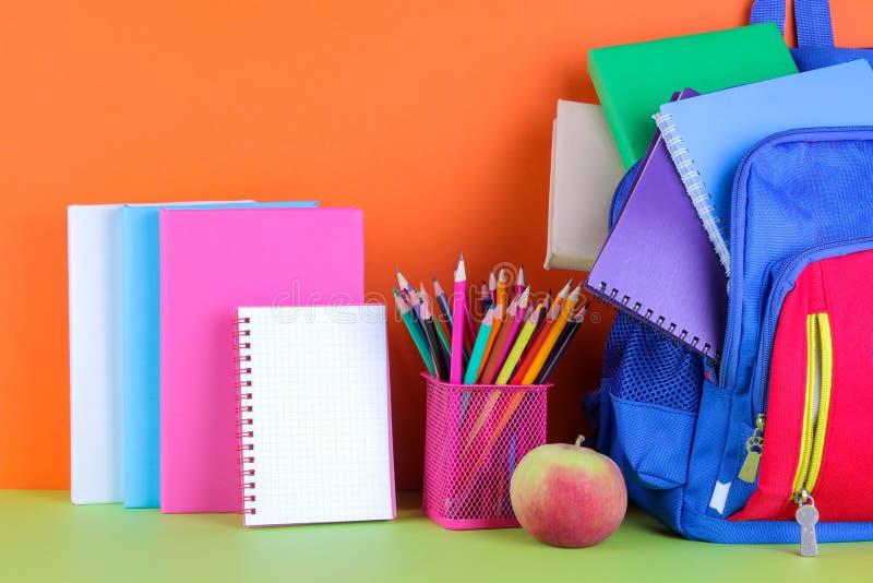 multi-colored schoollevering en een schoolrugzak op een heldere multi-colored achtergrond royalty-vrije stock foto's