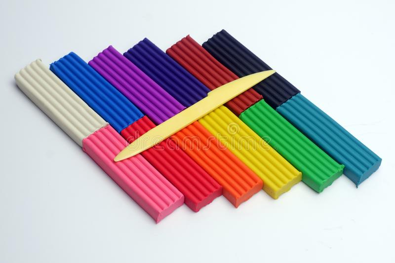 Multi-colored set of plasticine sticks and sculptural knife on white background royalty free stock image