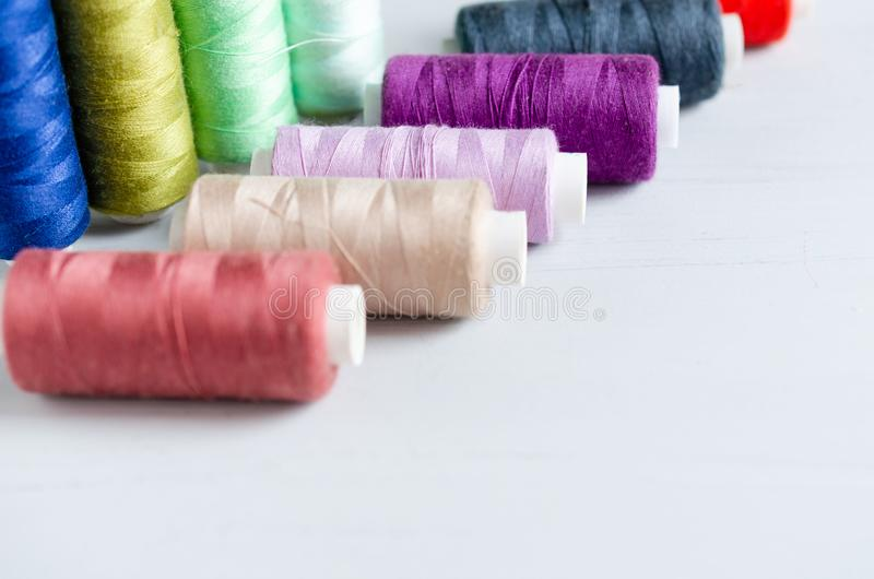 Multi-colored spools of sewing threads close-up. Craft and hobby concept royalty free stock images