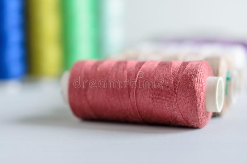 Multi-colored spools of sewing threads close-up. Craft and hobby concept stock images