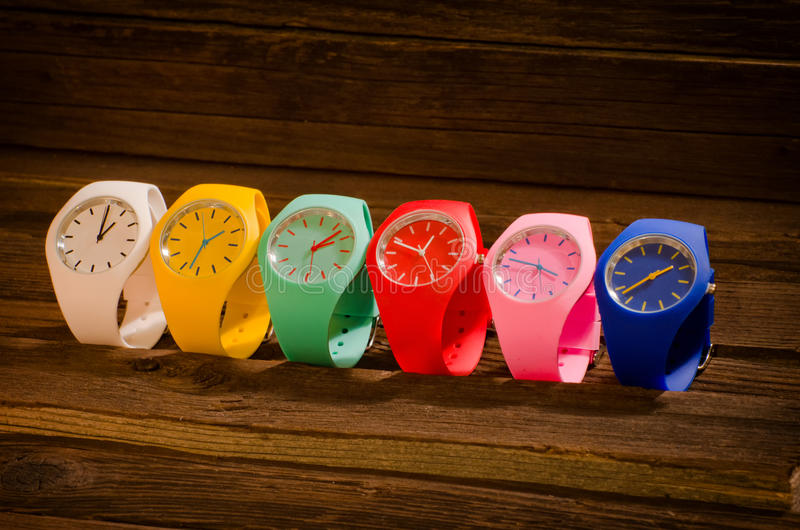 Multi-colored sports watch on a wooden background royalty free stock image