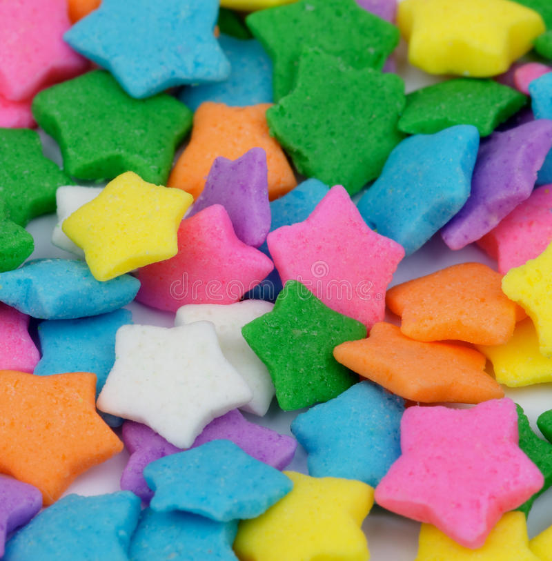 Multi Colored Stars Sprinkles. Background of Sugar Multi Colored Stars Dessert Toppings closeup. Focus on Centre stock photo