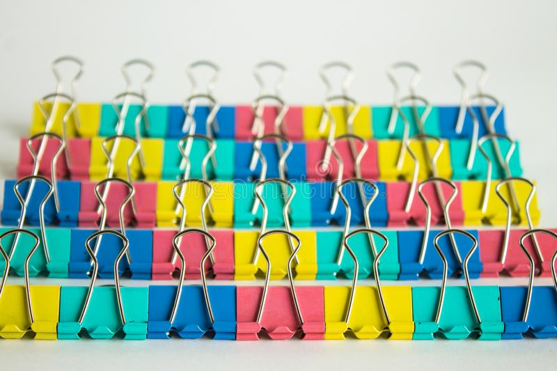 Multi-colored stationery clips in rows close-up on a neutral background royalty free stock photo