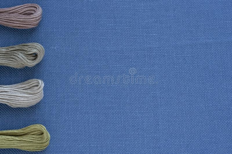 Multi-colored threads for embroidery on blue canvas. Place for text stock photos