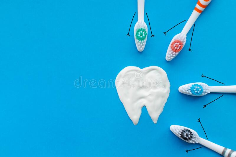 Multi-colored toothbrushes in the form of cartoon characters on a blue background with a tooth pattern drawn with toothpaste. The concept of family hygiene royalty free stock images