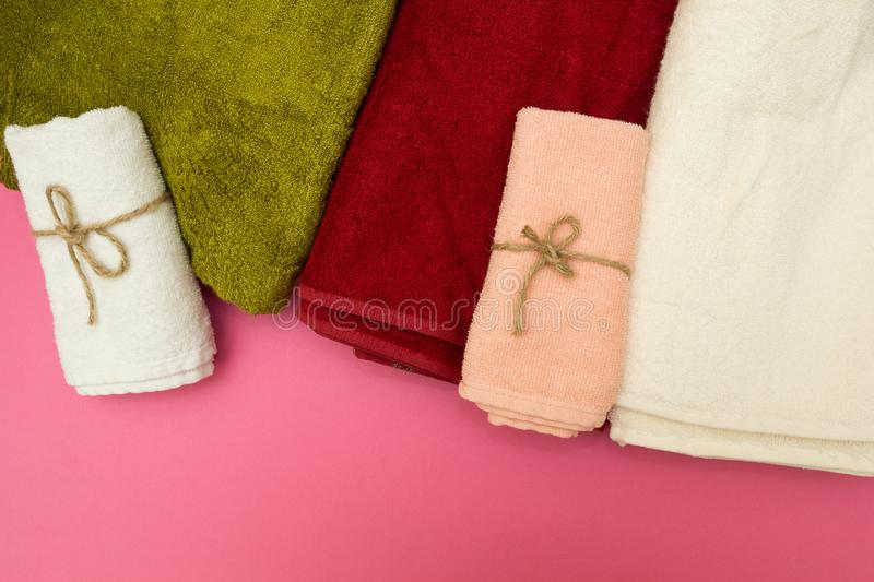 Multi-colored towels on a pink background stock photo