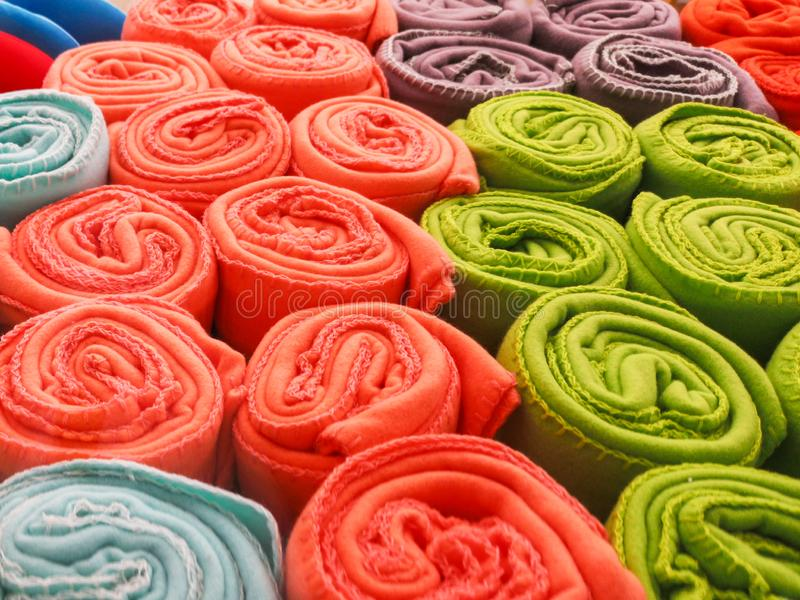 Multi-colored towels rolled into a tube lie on each other on the shelf. Multi-colored fabric rolled into a tube royalty free stock photo