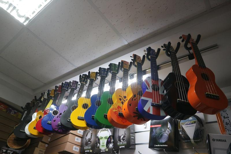 Multi-colored ukulele guitars in a musical instrument store stock photo