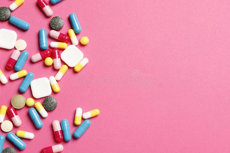 Multi-colored vitamins on a pink background royalty free stock image