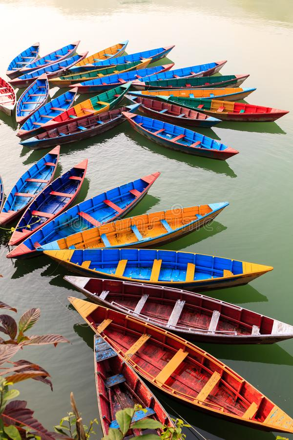 Multi-colored wooden boats on the Phewa lake, Pokhara, Nepal.  stock images