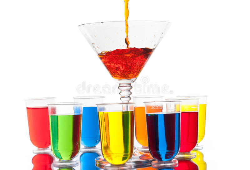 Multi-coloured alcohol shots and martini glass on white royalty free stock image