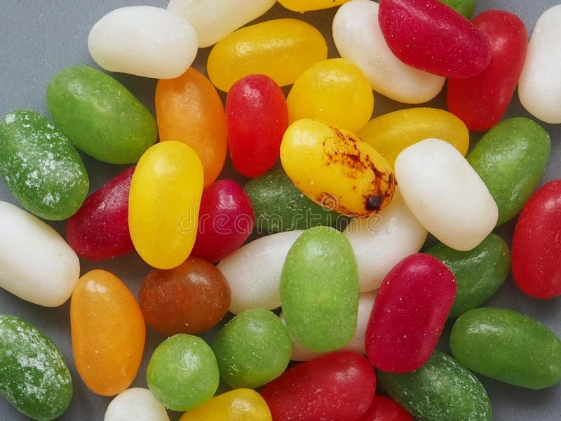 Multi coloured jelly bean sweets. Grey background colorful confectionery pile heap sugar unhealthy diabetes easter group jellybean flavour bonbon candy treat royalty free stock photo