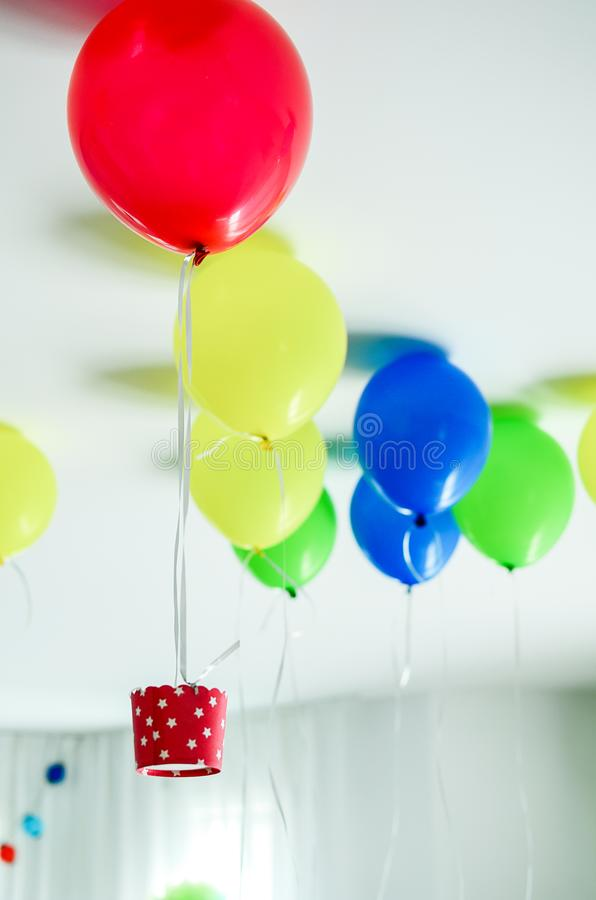 Multi-coloured kids birthday party Rainbow themed. Colourful balloons flying at the ceiling decorated like hot air balloons. royalty free stock image