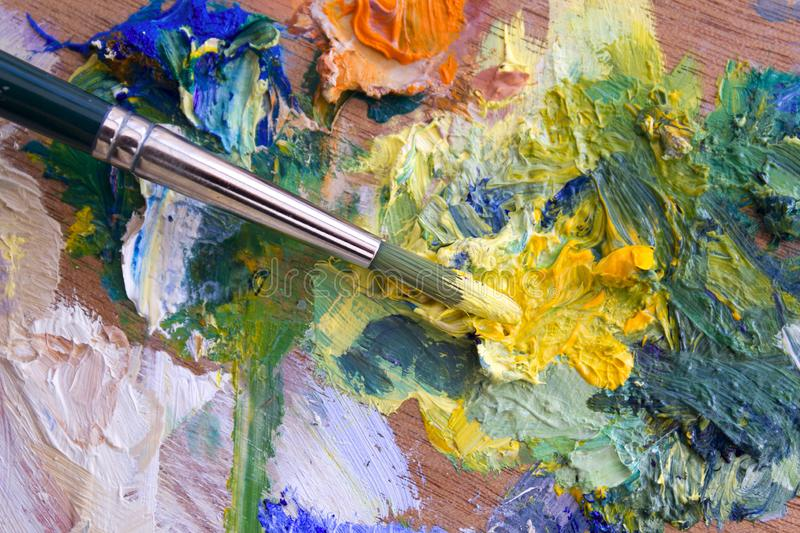 Multi-coloured palette. Vibrant multi-coloured artists oil or acrylic paints palette and paintbrush stock photo