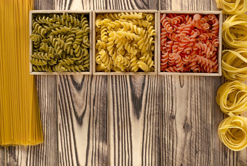 Multi-coloured pasta in the form of spirals lies in square wooden boxes that stand on a table stock image