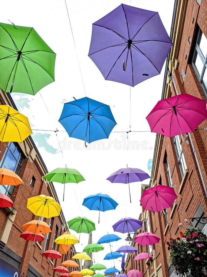 Multi coloured umbrellas floating in the sky royalty free stock photo