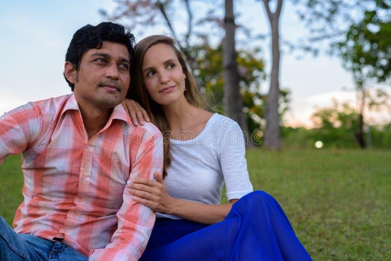 Multi coppie etniche che si siedono e che pensano sul prato nell'amore a fotografia stock libera da diritti