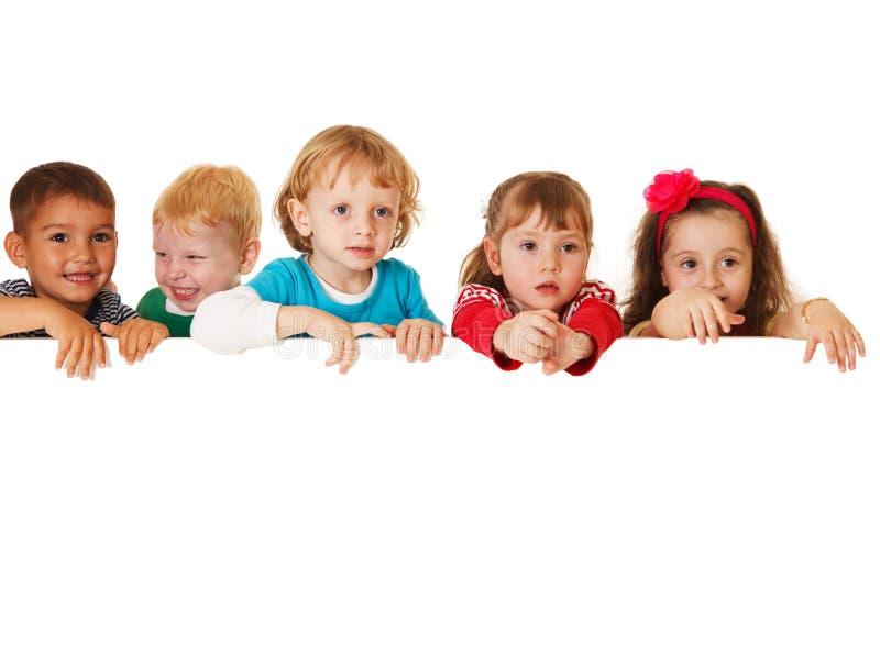 Multi crianças étnicas que guardam um cartaz vazio imagens de stock royalty free